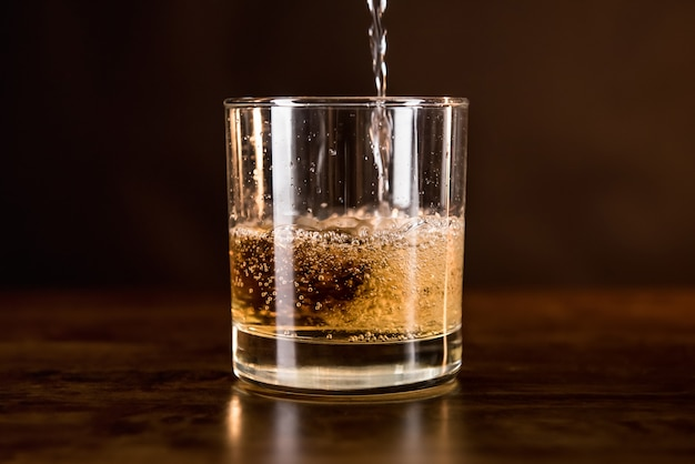 Whisky drink being poured in into the glass on wooden counter bar Premium Photo