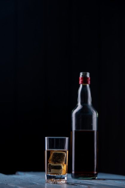Whisky glass and bottle on wooden table Free Photo