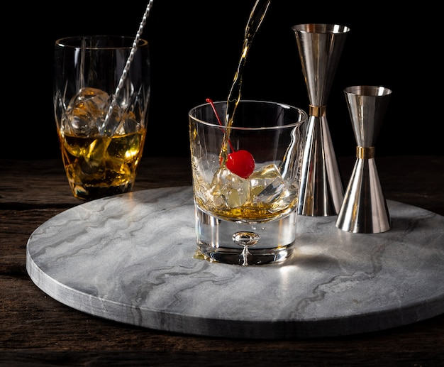 Whisky pouring in glass with cherry and jigger bartender Premium Photo