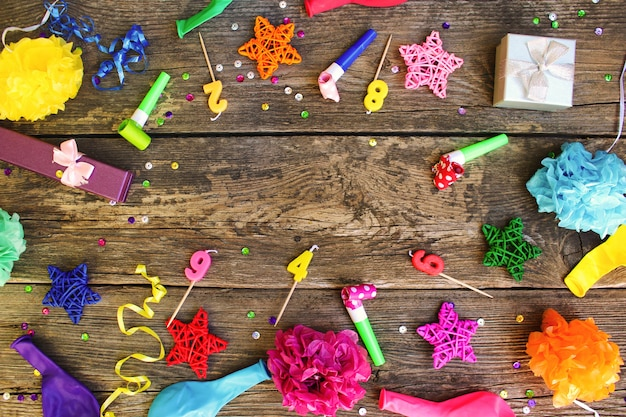 Whistles, balloons gifts, candles, decoration on old wooden background. concept of children's birthday party. top view. flat lay. Premium Photo