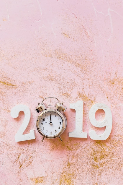 White 2019 inscription with clock on pink table Free Photo