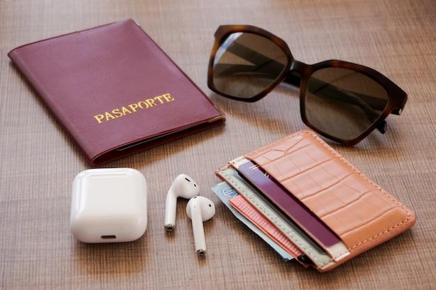 White air pods, red passport, wrist watch, brown sun glasses, wallet, cash money Premium Photo