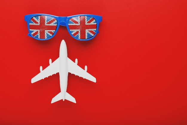白い飛行機とイギリスの国旗とサングラス。イギリスへの旅行。 Premium写真