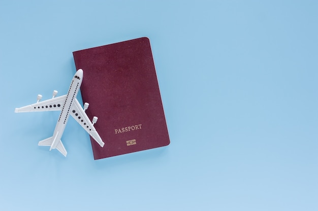 White airplane model with passport on blue for travel and journey concept Premium Photo