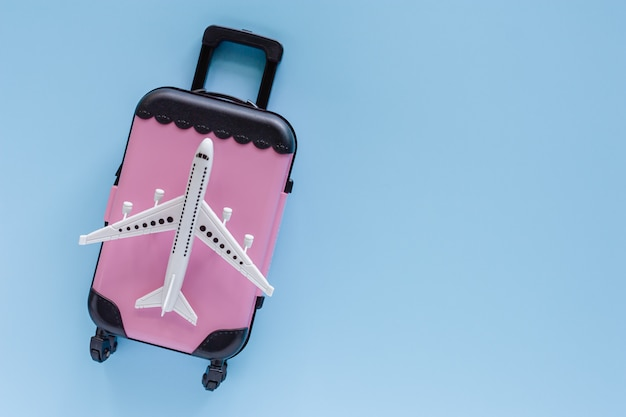 White airplane model with pink suitcase on blue for travel and journey concept Premium Photo