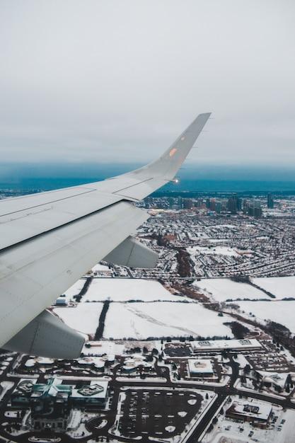 昼間の都市の上の白い飛行機の翼 無料写真