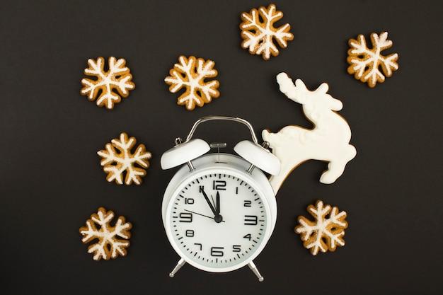 Белый будильник и рождественские пряники Premium Фотографии