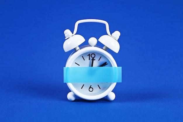 White alarm clock blue. blank sticky note on clock. space copy. minimal concept. Premium Photo