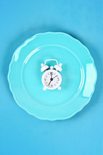 White alarm clock in blue empty plate. Premium Photo
