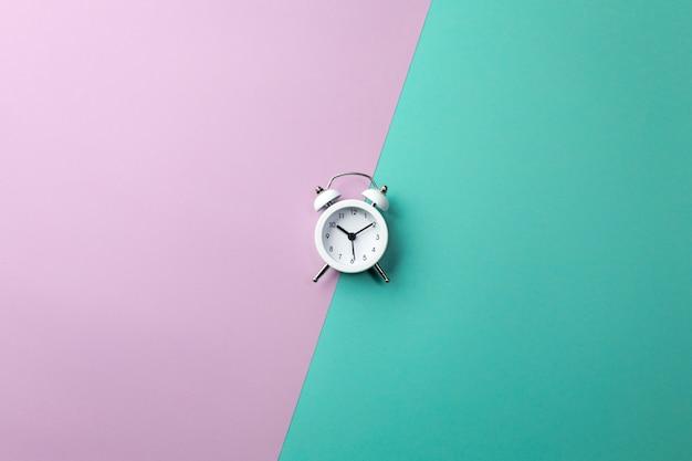 White alarm clock on colorful. concept in minimal style Premium Photo