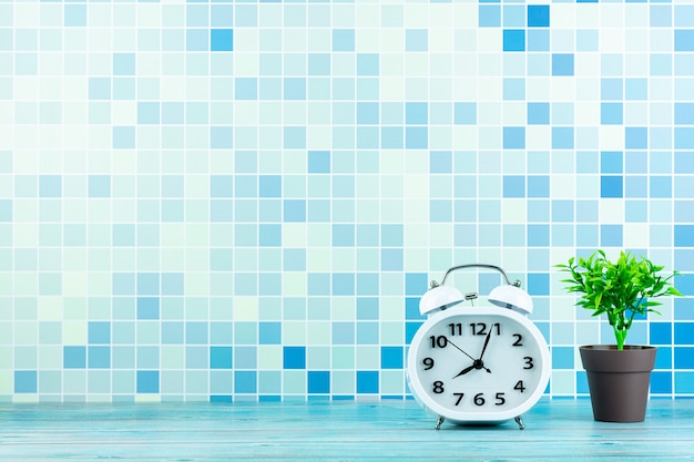 White alarm clock front a blue tile wall. Premium Photo