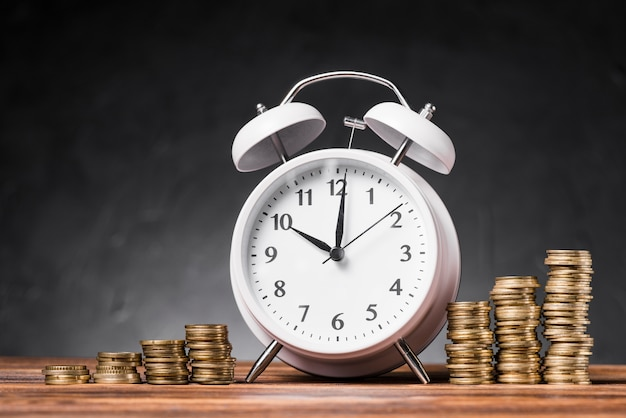 White alarm clock between the increasing stack of coins on wooden table against gray background Free Photo