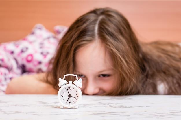 Белый будильник стоит на столе проснувшейся девушки Premium Фотографии