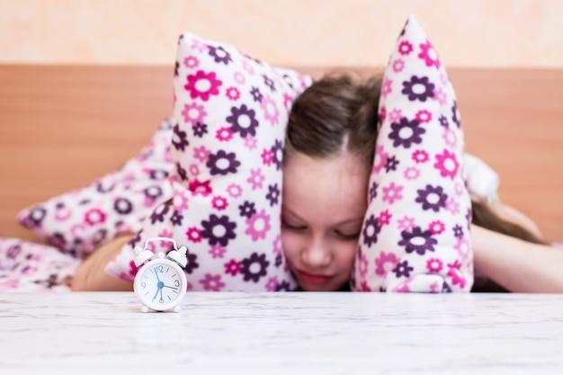 Белый будильник стоит на столе на фоне девушки, закрывающей уши подушками Premium Фотографии
