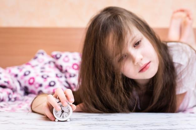 Белый будильник стоит на столе на фоне просыпающейся девушки Premium Фотографии