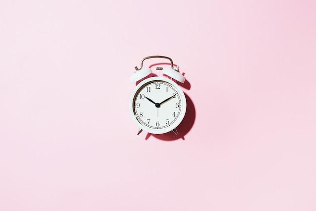 White alarm clock with hard shadow on pink background. Premium Photo