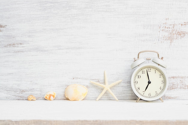 White alarm clock with starfish, sea shells on white rusty wood background. background concept for summer time holiday vacation, sea beach travel vacation time. Premium Photo