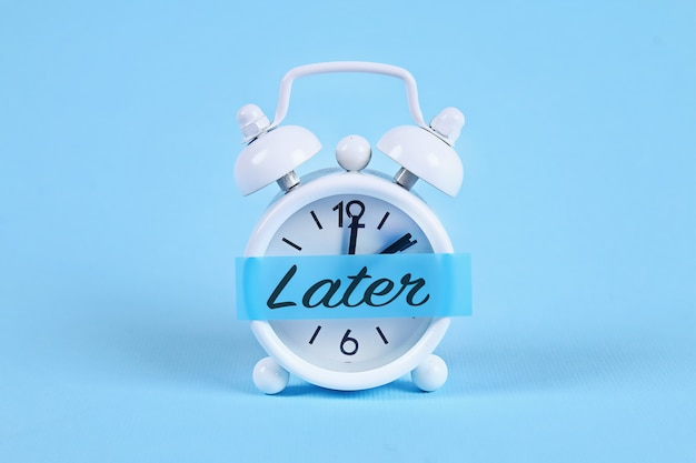 White alarm clock with a sticky note with text later. Premium Photo