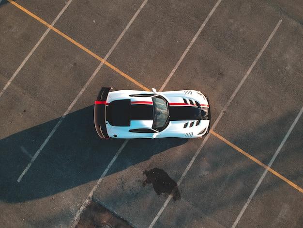 Бело-черная машина на асфальтированной дороге Бесплатные Фотографии