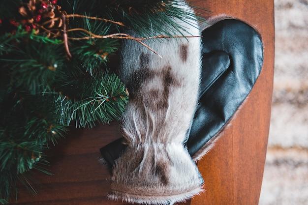 Черно-белые перчатки возле елки с коричневой шишкой Бесплатные Фотографии
