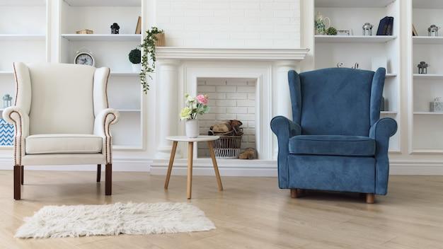 リビングルームの暖炉の前で白いモダンなテーブルと白と青のアームチェア Premium写真