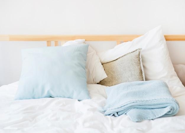 Белое и синее постельное белье на кровати Premium Фотографии