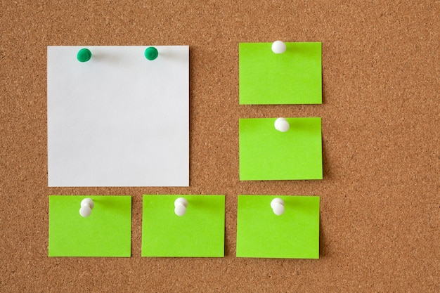 コルクボード上のメモ用の白と緑の紙5枚。ビジネスコンセプトです。コピースペース。 Premium写真