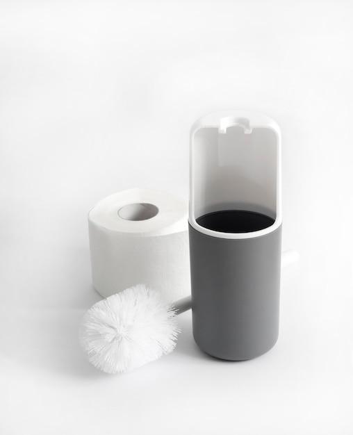 Белый и серый пластиковый туалетный ершик и рулон туалетной бумаги на белой поверхности Premium Фотографии