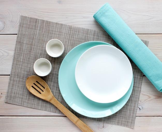 白とターコイズのプレート、木製のキッチンスプーン Premium写真