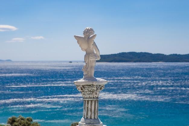 ぼやけた海と白い天使像を後ろから撮影 無料写真
