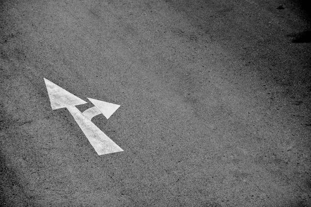 White arrow painted on asphalt road Premium Photo