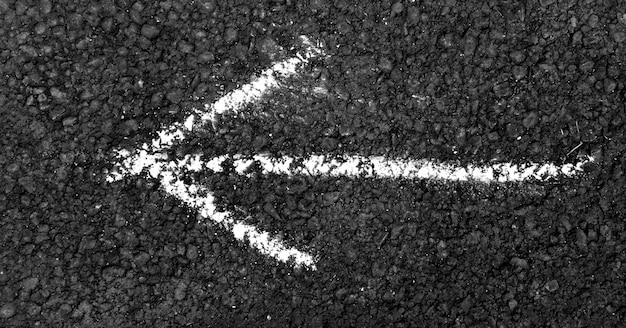 White arrow painted on asphalt road Photo | Premium Download