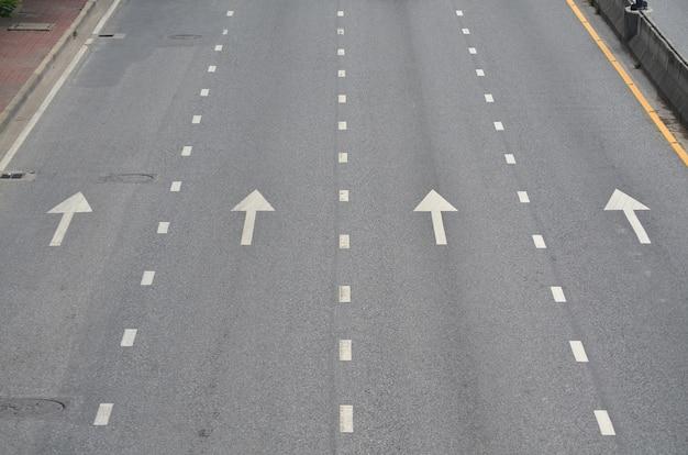 The white arrow on the road background Premium Photo