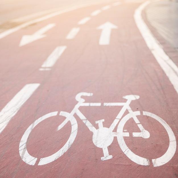 White asphalt bike lane with directional sign Free Photo