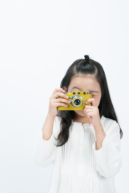 In the white background, a child is filming the front with a camera. Premium Photo