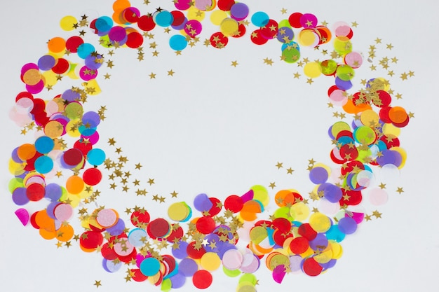 On a white background colored confetti and golden stars are lined up in a circle Premium Photo