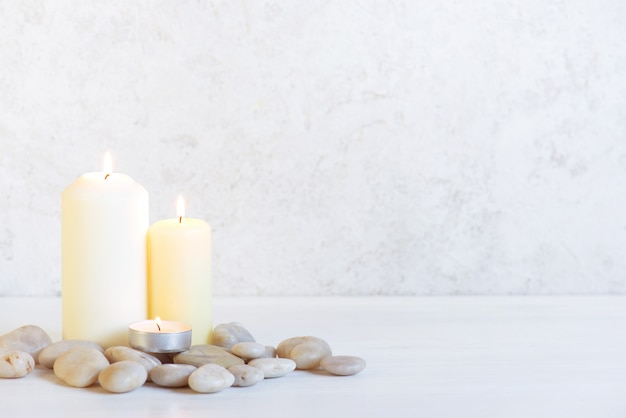 White background with three burning candles and stones Premium Photo