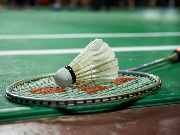 White badminton shuttlecock and racquet on a green court. Premium Photo