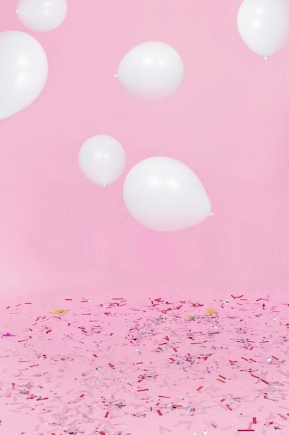 ピンクの背景に対する紙吹雪上の空気中の白い風船 Premium写真