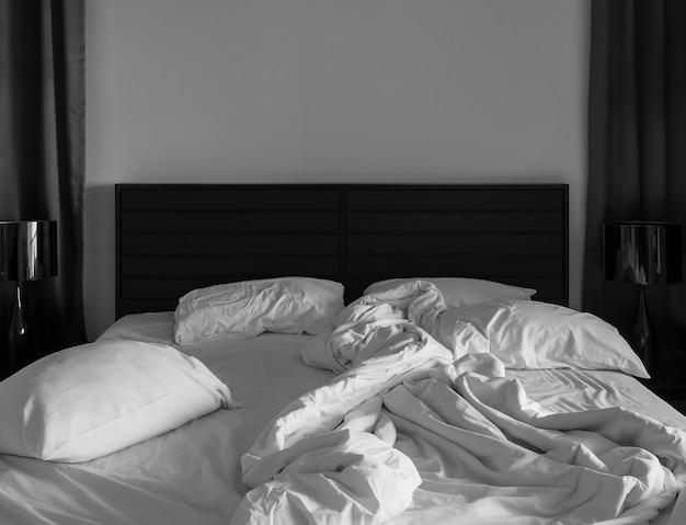 Белая простыня и подушки перепутались в темной спальне Premium Фотографии