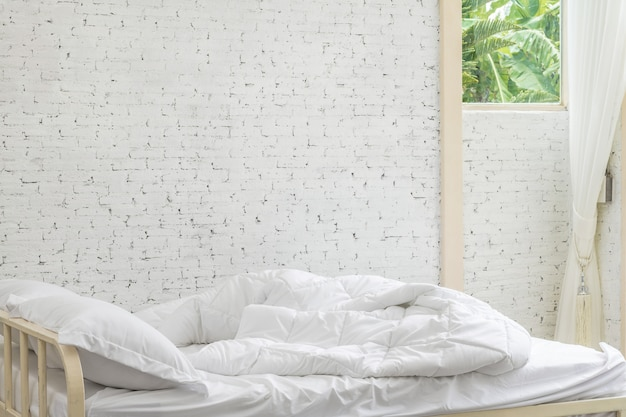 White bedding sheets and pillow in white room background. Premium Photo