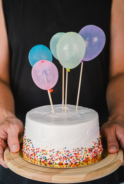 White birthday cake and colorful balloons over light grey.food concept anniversary. Premium Photo