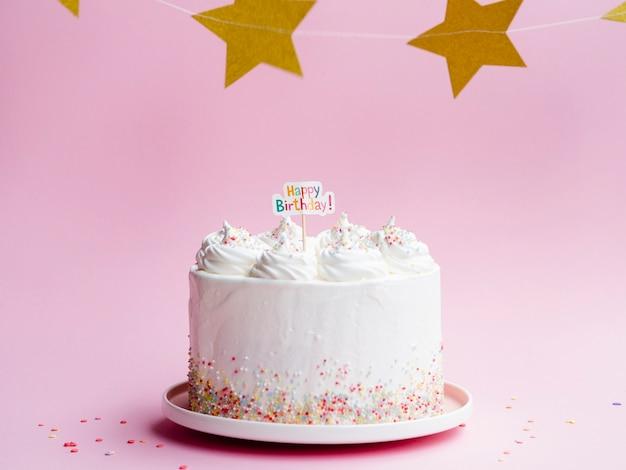 White birthday cake and golden stars Free Photo