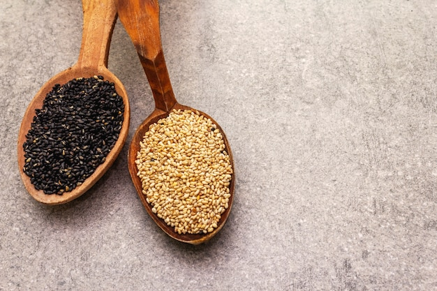 White and black sesame seeds in wooden spoons Premium Photo