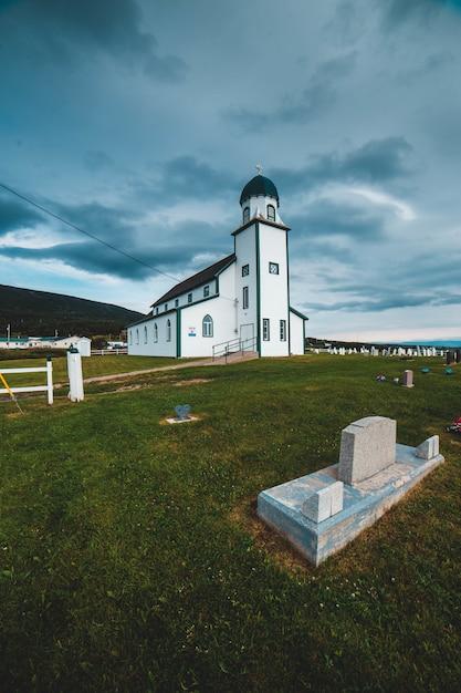 Chiesa di legno bianca e nera sotto le nuvole grigie durante il giorno Foto Gratuite