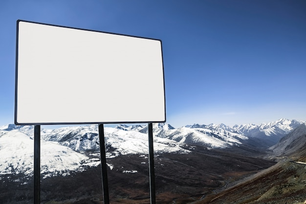 White blank billboard with a view of clear blue sky and snow capped mountain range. Premium Photo