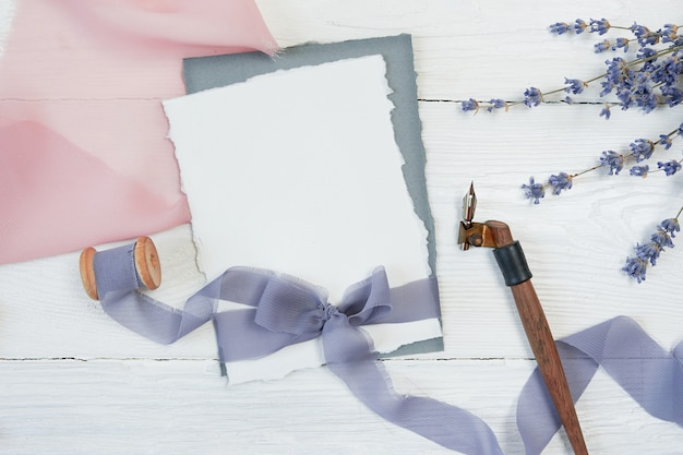 White blank card ribbon bow on a background of pink and blue fabric with lavender flowers and calligraphic pen Premium Photo