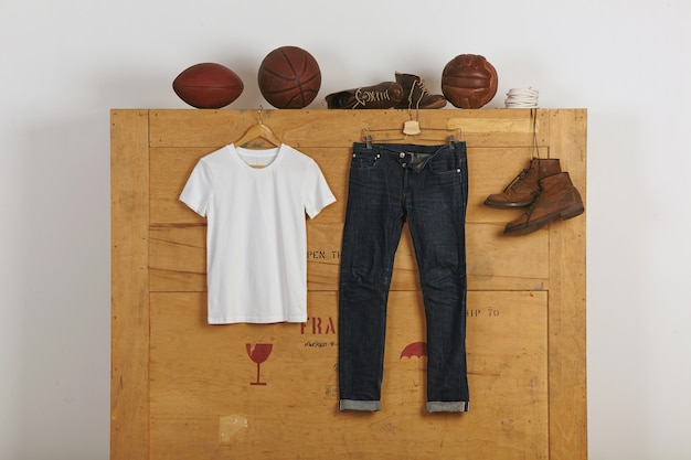 日本のセルヴィッチジーンズと革靴の近くに白い空白の綿の渇きが木製の大きなカーゴボックスにあり、その上にビタージュプレイボールがあります 無料写真