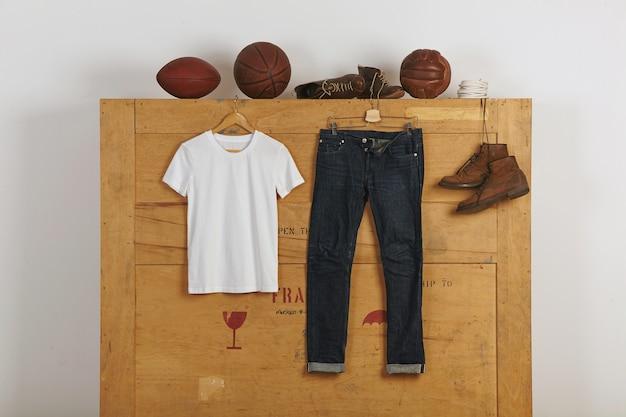 Gonna in cotone bianco bianca presentata vicino a jeans giapponesi con cimosa e scarpe in pelle su una grande scatola di carico in legno con palline di vitage sulla parte superiore Foto Gratuite