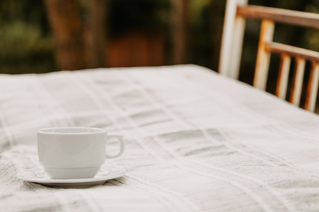 A white blank cup of coffee on a bed Premium Photo